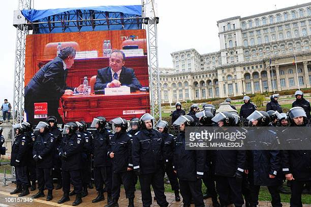 Romanian police forces secure the perimeter in front of a giant screen showing Pime Minister Emil Boc during a Trade Union protest outside the...