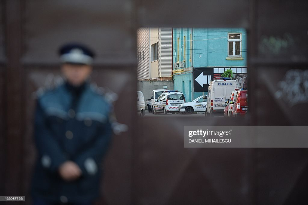 A Romanian police officer guard the entrance of the nightclub Colectiv in Bucharest on October 31, 2015, a day after a fire broke up inside the club. At least 27 people were killed and more than 160 injured after a fire ripped through a nightclub in Bucharest late on Friday, in one of the worst accidents to hit the Romanian capital. MIHAILESCU