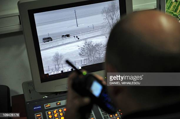 A Romanian police officer talks with operational team as he observes suspicious activities along the border on a thermal vision camera during a drill...
