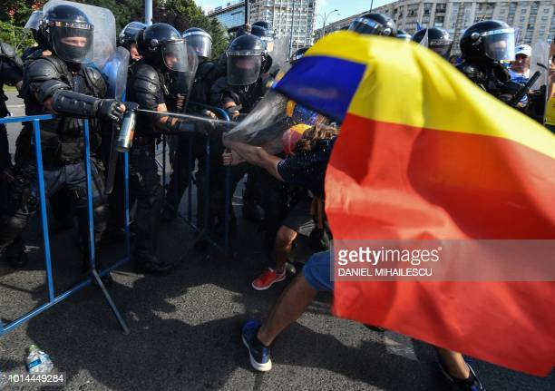 Romanian police scuffle with protesters and spray tear gas against them during an antigovernment protest in front of the Romanian Government...