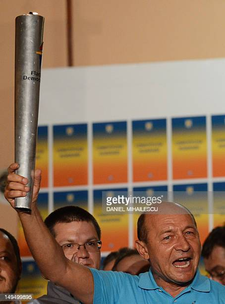 Romanian President Traian Basescu holds The Democracy Torch as he addresses reporters at his electoral campaign headquarters in Bucharest July 29...
