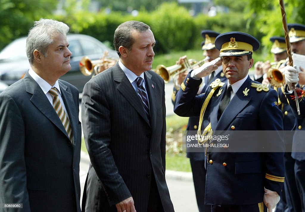 Romanian Prime Minister Adrian Nastase (L) and his Turkish counterpart Recep Tayyip Erdogan (C) review an honour guard at Victoria Palace, the Romanian government headquarter in Bucharest 20 May 2004. Erdogan is in a two days official visit in Romania.