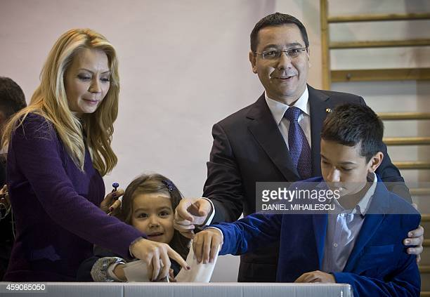 Romanian Prime Minister and presidential candidate Victor Ponta and his wife Daciana Sarbu flanked by their children vote at a polling station in...