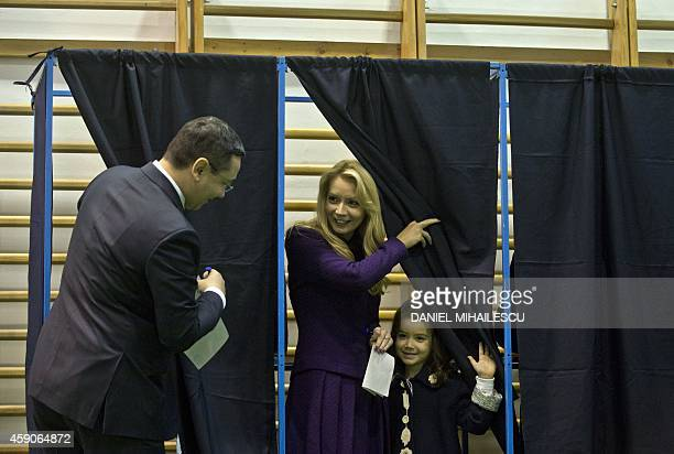 Romanian Prime Minister and presidential candidate Victor Ponta watches his wife Daciana Sarbu and their child who leave a polling booth at a polling...
