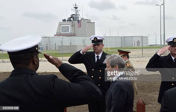 Romanian Prime Minister Dacian Ciolos looks on as US Army servicemen salute during the inauguration ceremony of the Aegis Ashore Romania facility at...