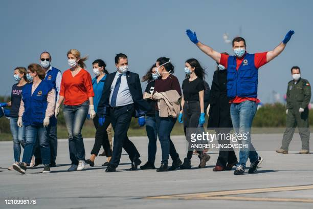 Romanian Prime Minister Ludovic Orban welcomes a team of doctors and emergency service workers who have been on a mission in Italy helping with the...