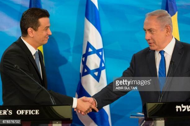 Romanian Prime Minister Sorin Grindeanu and Israeli Prime Minister Benjamin Netanyahu shake hands during a joint press conference at the Prime...