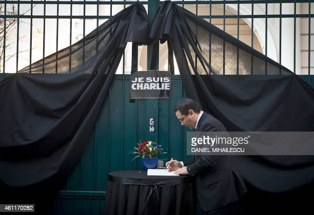 Romanian Prime Minister Victor Ponta writes on a condolence book displayed outside the French embassy to Bucharest on January 8 2015 a day after...