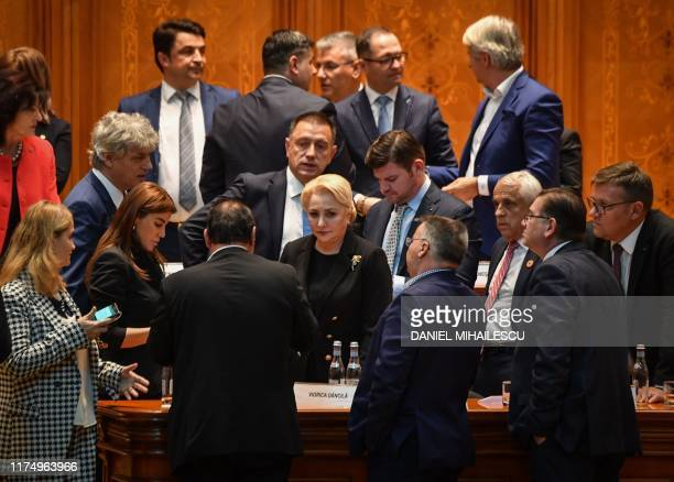 Romanian Prime Minister Viorica Dancila is sourrounded by members of her cabinet after the government was toppled by a nonconfidence vote at the...