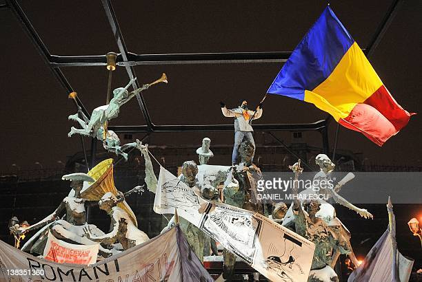 A Romanian protester stands on a monument waving a national flag as he shouts antipresidential slogans during a demonstration in Piata Universitatii...