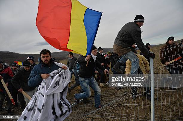 Romanian protesters tear down the fence of the exploring perimeter of US energy giant Chevron in Pungesti Romania on December 7 2013 Around 500 anti...