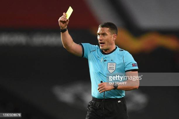 Romanian referee Istvan Kovacs shows a yellow card to Manchester United's French midfielder Paul Pogba during the UEFA Europa league quarter final,...