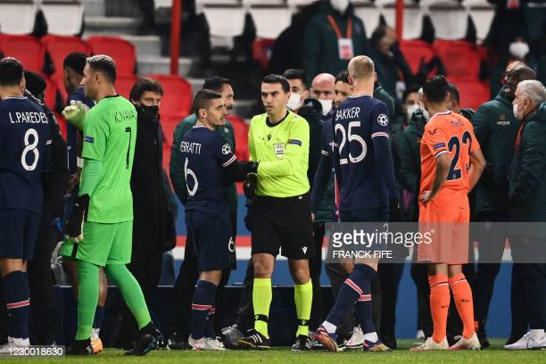 Romanian referee Ovidiu Hategan passes by Paris Saint-Germain's Italian midfielder Marco Verratti after the game was suspended amid allegations of...