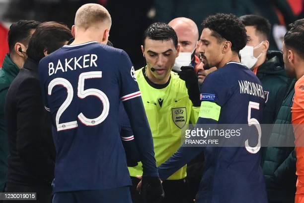 Romanian referee Ovidiu Hategan passes by Paris Saint-Germain's Brazilian defender Marquinhos after the game was suspended amid allegations of racism...