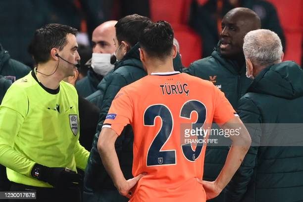 Romanian referee Ovidiu Hategan talks to Istanbul Basaksehir FK staff members during the UEFA Champions League group H football match between Paris...