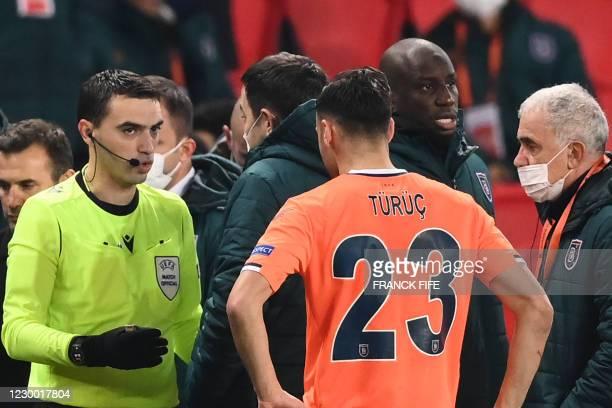 Romanian referee Ovidiu Hategan talks to Istanbul Basaksehir FK staff members past Istanbul Basaksehir's French forward Demba Ba during the UEFA...