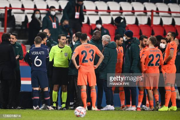 Romanian referee Ovidiu Hategan talks to Istanbul Basaksehir's staff members past Istanbul Basaksehir's French forward Demba Ba during the UEFA...