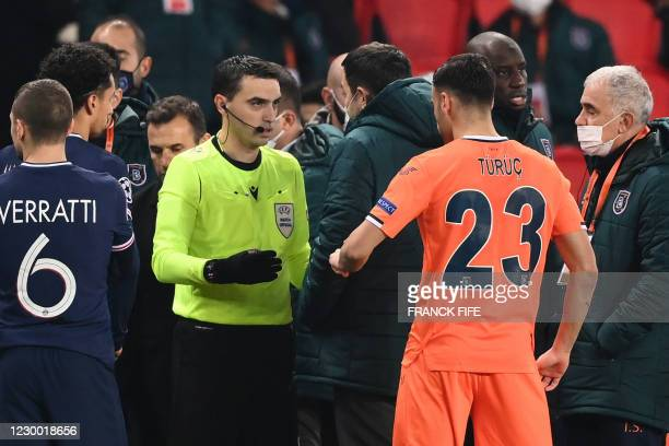 Romanian referee Ovidiu Hategan talks to Istanbul Basaksehir's staff members past Istanbul Basaksehir's French forward Demba Ba after the game was...