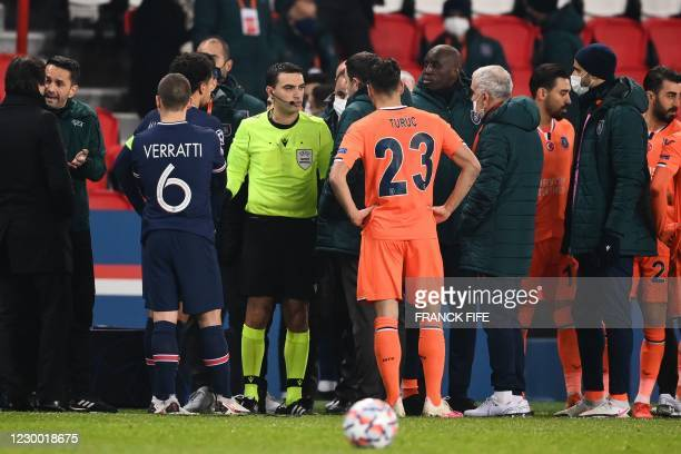Romanian referee Ovidiu Hategan talks to Istanbul Basaksehir's staff members after the game was suspended amid allegations of racism by one of the...