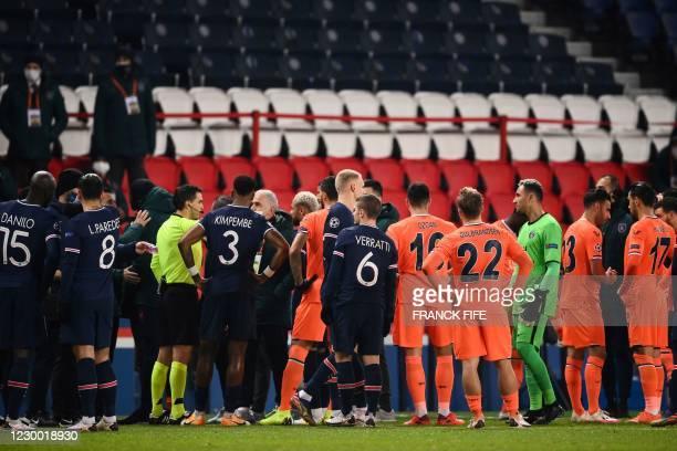 Romanian referee Ovidiu Hategan talks to Istanbul Basaksehir's staff members during the UEFA Champions League group H football match between Paris...