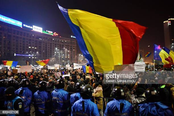 Romanian riot police stand guard as people demonstrate against controversial decrees to pardon corrupt politicians and decriminalize other offenses...