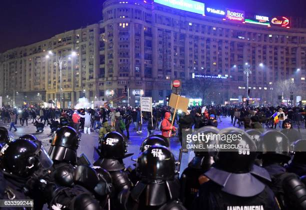 Romanian riot police stand guard as people take part in a protest against controversial decrees to pardon corrupt politicians and decriminalize other...