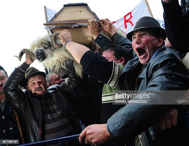 Romanian shepherds shout antigovernment slogans while they hold a sheep head in the front of the Romanian Finance Ministry headquarters in Bucharest...
