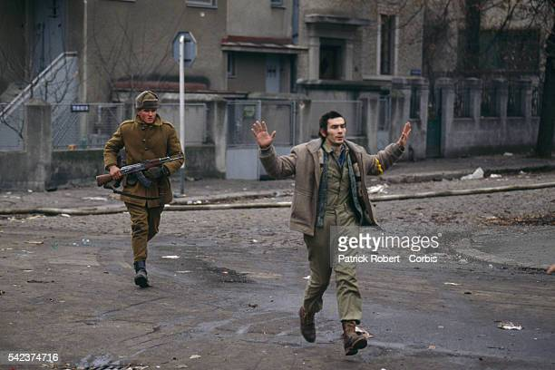 A Romanian soldier chases a man who holds his arms up in surrender during the December 1989 uprising which marked the end of Communist dictator...