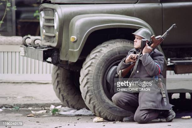 A Romanian soldier hides behind a military truck during fights to overthrow the Socialist Republic of Romania on December 24 1989 in Bucharest as the...