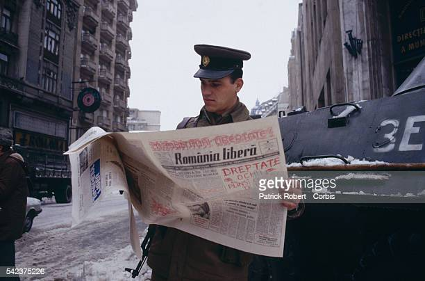 A Romanian soldier reads the Romania Libera newspaper on a Bucharest street days after the December 1989 uprising which marked the end of dictator...