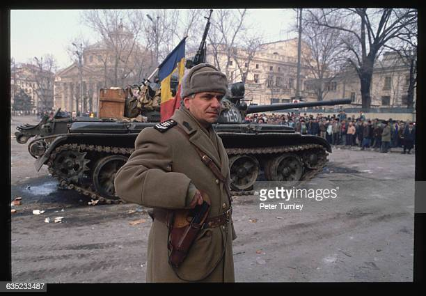 A Romanian soldier walks his rounds in Palace Square near a tank and the assembled crowds during the revolution of December 1989 A Romanian flag with...