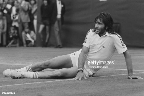 Romanian tennis player Ilie Nastase resting on the tennis court at Wimbledon Championships Men's Singles at the All England Lawn Tennis and Croquet...