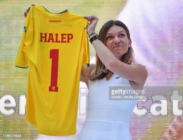 Romanian tennis player Simona Halep, winner of Wimbledon WTA Tournament holds up a Romanian national football team jersey preented to her by the...