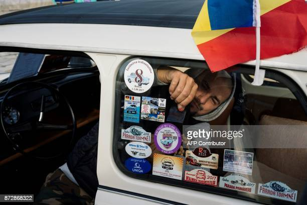A Romanian Trabant owner sticks sticker on his car windshield during a gathering to celebrate the 60th anniversary of the car in the town of Pavel...