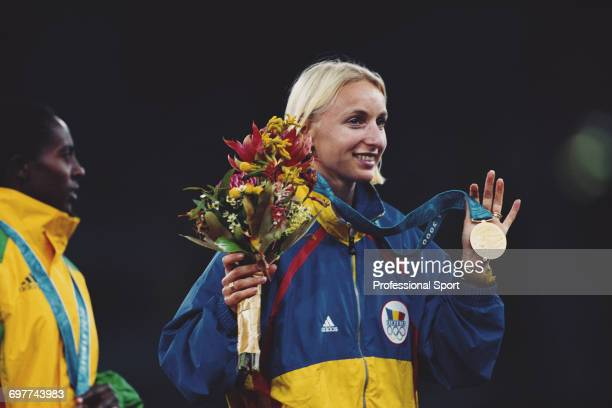 Romanian track athlete Gabriela Szabo displays her gold medal on the medal podium after crossing the finish line in first place to win the gold medal...