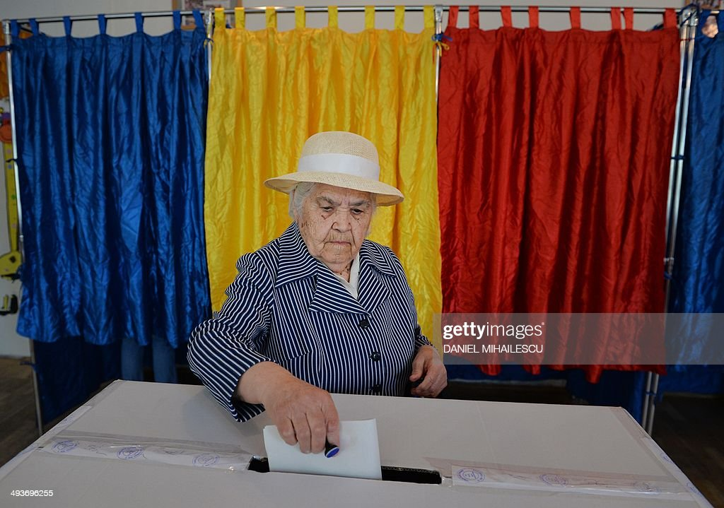 A Romanian woman casts her ballot for the European Parliament elections near booths featuring the national colors of Romania at a polling station in Bucharest on May 25, 2014. MIHAILESCU