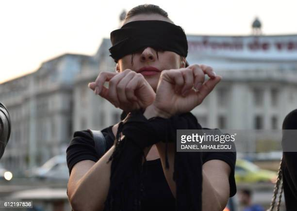 A Romanian woman shows support with Polish women on strike during a flashmob in Piata Universitatii square in Bucharest on October 3 2016 Thousands...