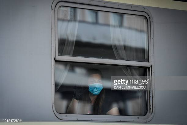 Romanian woman wearing a protective face mask waves from inside a train car at a railway station in Timisoara city, western Romania, on May 10 as...