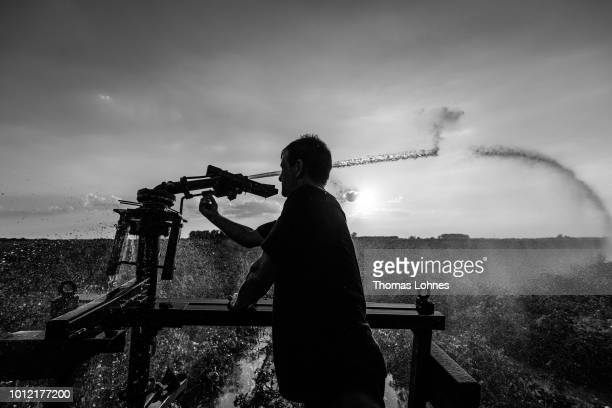 A Romanian worker adjusts an irrigation plant at a potato field on August 6 2018 in Eschollbruecken near Darmstadt Germany Farmers are fighting...