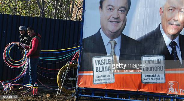 Romanian workers install fiberglass cables next to a DemocratLiberal Party banner showing candidates Vasile Blaga and Catalin Croitoru in Bucharest...