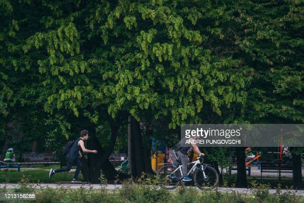 Romanians enjoy a day in a park, that has just reopened, in Bucharest's city center on the first day that the lockdown imposed to stop the spread of...