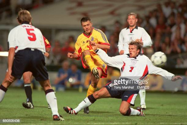 Romania's Adrian Ilie gets in a shot before England's David Beckham can make a tackle