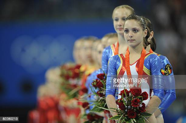 Romania's Anamaria Tamirjan stands on the podium with her teammates after winning the bronze in the women's team final of the artistic gymnastics...