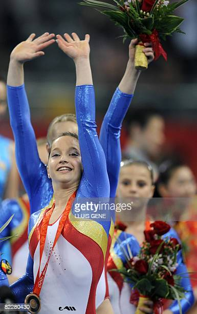 Romania's Anamaria Tamirjan waves to the crowd after she and her teammates won the bronze in the women's team final of the artistic gymnastics event...
