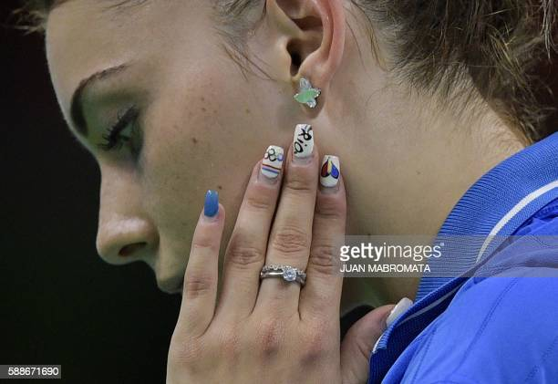 Romania's Bernadette Szocs' Rio 2016 Olympic Gamesthemed nail polish is pictured during a women's team qualification round table tennis match against...