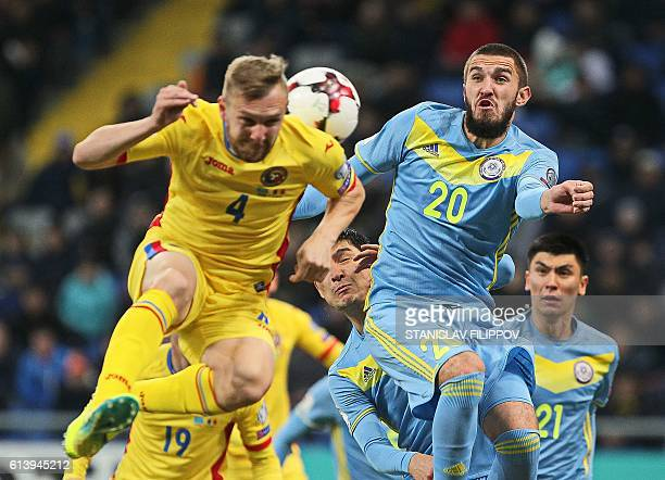 Romania's Cosmin Moti vies for the ball with Kazakhstan's Sergei Khizhnichenko during the WC 2018 football qualification match between Kazakhstan and...