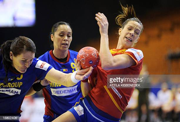 Romania's Cristina Neagu and Aurelia Bradeanu push Spain's Begona Fernandez during the 2012 EHF European Women's Handball Championship Group II match...