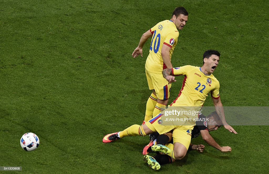 TOPSHOT - Romania's defender Cristian Sapunaru (C) is challenged by Albania's defender Andi Lila during the Euro 2016 group A football match between Romania and Albania at the Parc Olympique Lyonnais stadium in Lyon on June 19, 2016. / AFP / JEAN