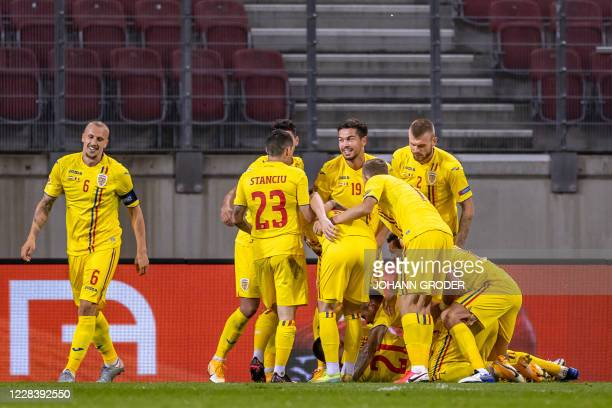 Romania's defender Dragos Grigore is mobbed on the ground by his team-mates after scoring during the UEFA Nations League football match between...