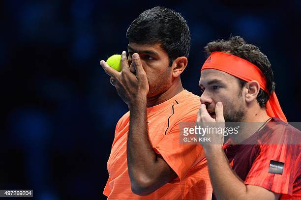 Romania's Florin Mergea and India's Rohan Bopanna discuss tactics against US player Mike Bryan and US player Bob Bryan during their men's doubles...